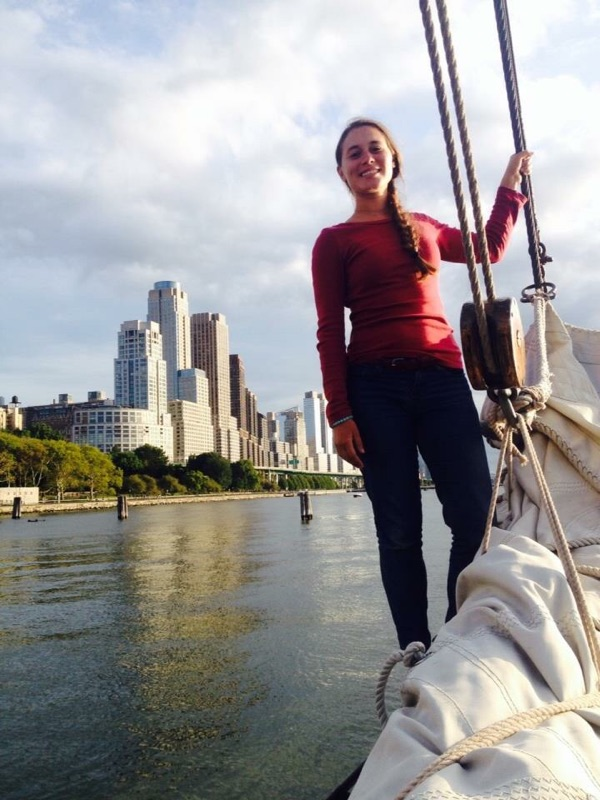 Melanie Colby standing on the tip of a bowsprit, holding on to a stay. It is a sunny day and the water is calm. There are tall buildings and trees in the background.