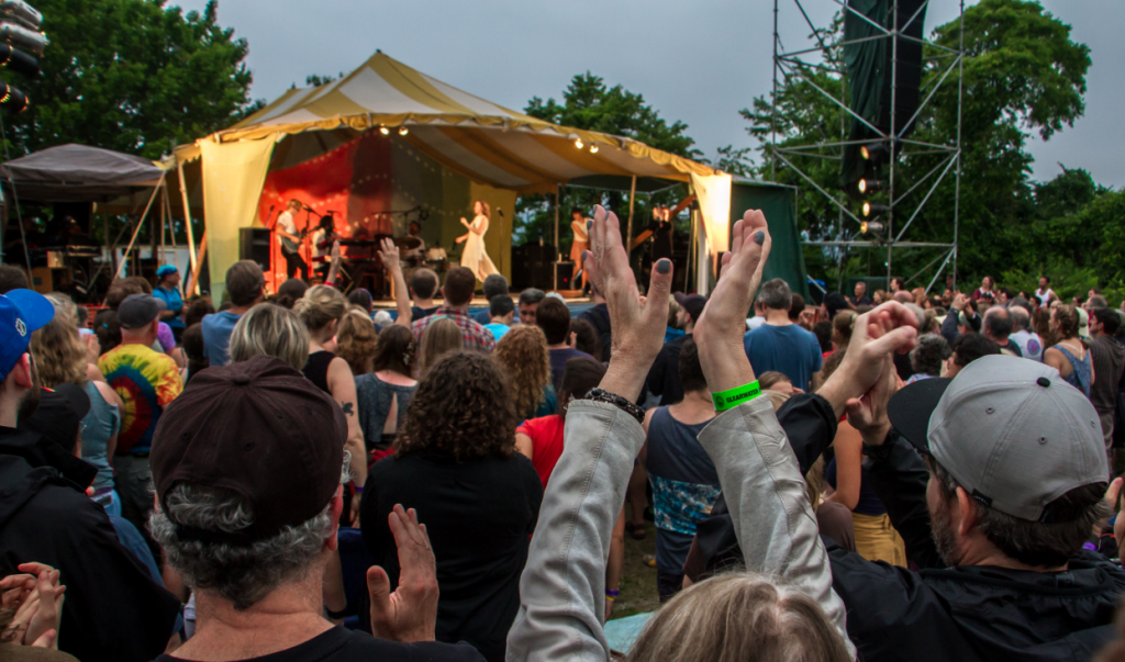 An image of a the crowd in front of a stage at the Great Hudson River Revival music festival.  People in the crowd are raising their arms above their heads to clap.  On stage, the band Lake Street Dive is performing.