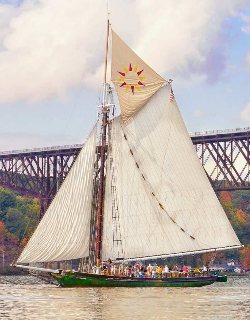 An image of the Hudson River Sloop Clearwater sailing by the Walkway over the Hudson near Poughkeepsie, new York. The sails are set, including the topsail, which has a red and yellow sun pattern on it.