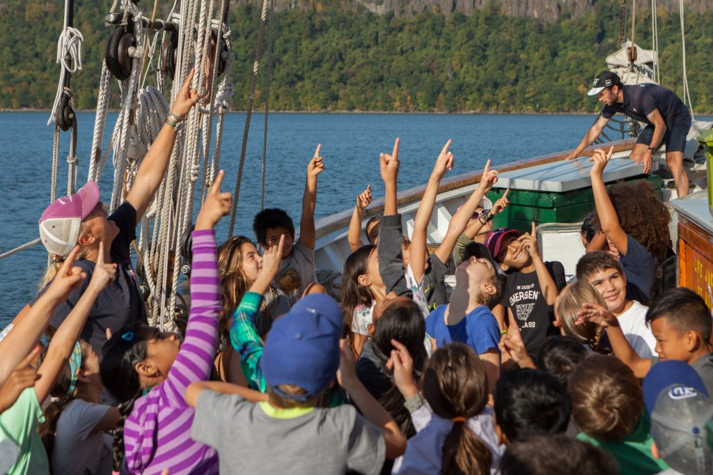 A group of schoolchildren and educators pointing upwards while seated on the port deck of the sailboat Hudson River Sloop Clearwater on a sunny day.