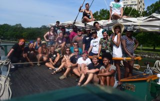An image of the participants in the 2017 LGBTQ+Allies Youth at the Helm program gathering on the stern of the Clearwater and on top of the boom.